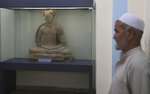 In this Saturday, Aug. 17, 2019 photo, a complete figure of a seated Buddha dating from the third or fourth century is on display at the National Museum of Afghanistan in Kabul, Afghanistan. As an Afghanistan peace deal nears, museum workers rush to restore art shattered by Taliban amid fears over its return. Conservator Sherazuddin Saifi remembers the day the Taliban arrived at the national museum in 2001, a period of cultural rampage in which the world's largest standing Buddha statues in Bamyan province were dynamited, to global horror. (AP Photo/Rafiq Maqbool)