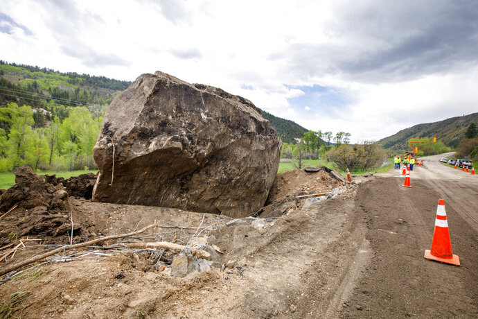 FILE - In this May 27, 2019 file photo, an 8.5 million pound boulder rests next to Colorado State Highway 145 after falling from nearly 1,000 feet from the nearby ridge and destroying the pavement between Cortez and Telluride, Colo. The state has decided to keep the boulder where it is and re-route the highway around it, saving about $200,000 in blasting costs  (Hugh Carey/Summit Daily News via AP, File)