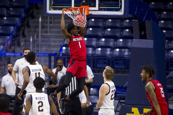 North Carolina State's Dereon Seabron (1) dunks over Notre Dame's Juwan Durham (11), Trey Wertz (2) and Dane Goodwin (23) during the second half of an NCAA college basketball game Wednesday, March 3, 2021, in South Bend, Ind. North Carolina State won 80-69. (AP Photo/Robert Franklin)