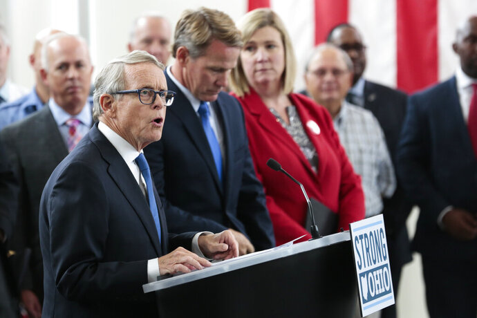 Ohio Gov. Mike DeWine unveils the STRONG Ohio Bill during a news conference Monday, Oct. 7, 2019 at the Ohio Department of Public Safety in Columbus, Ohio. Republican Gov. Mike DeWine's new proposals to address Ohio gun violence in the wake of the Dayton mass shooting don't include background-check requirements for gun sales or a so-called red-flag law to restrict firearms for people perceived as threats, despite his earlier support of those ideas. Instead, his administration detailed legislative proposals Monday intended to increase and improve background checks and ensure people don't have firearms if a court has deemed them to be a danger. (Joshua A. Bickel/The Columbus Dispatch via AP)