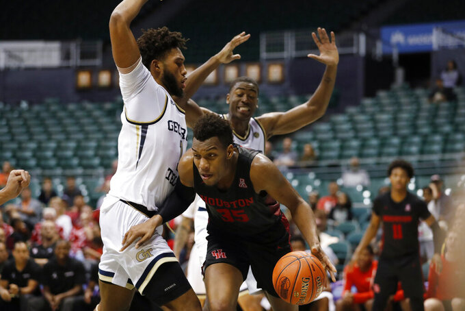 After grabbing a rebound, Houston forward Fabian White Jr. (35) tries to get past Georgia Tech forwards James Banks III. left, and Moses Wright during the second half of an NCAA college basketball game Monday, Dec. 23, 2019, in Honolulu. (AP Photo/Marco Garcia)