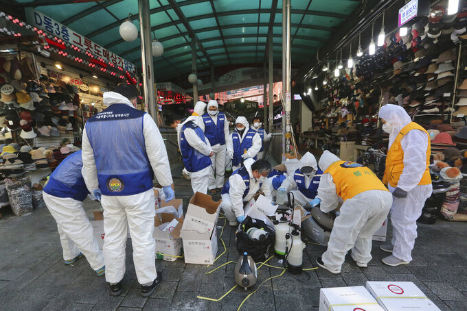 In this Feb. 5, 2020, photo, workers wearing protective gears prepare to spray disinfectant as a precaution against the coronavirus at Namdaemun Market in Seoul, South Korea. Even as cases and deaths from the new virus mount, fear is advancing like a tsunami - and not just in the areas surrounding the Chinese city of Wuhan, the center of the outbreak that has been declared a global health emergency.  (AP Photo/Ahn Young-joon)