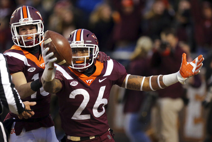 Virginia Tech defenders Jovonn Quillen (26) and Coleman Fox (16) celebrate recovering a blocked kick for a touchdown during the first half of an NCAA college football game against Virginia, in Blacksburg, Va., Friday, Nov. 23, 2018. (Matt Gentry/The Roanoke Times via AP)
