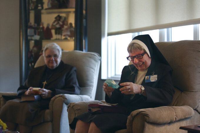 Sister Mary Charlene Ozanick, of the Felician Sisters of North America, right, laughs at a motivational quote written on a bar of soap given to her by a fellow nun at St. Anne Home in Greensburg, Pa., on Thursday, March 25, 2021. (AP Photo/Jessie Wardarski)