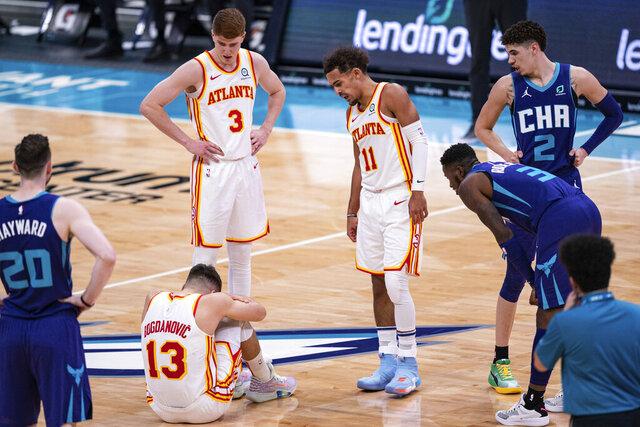 Atlanta Hawks guard Bogdan Bogdanovic (13) sits on the court after being fouled by Charlotte Hornets guard LaMelo Ball (2) during the first half of an NBA basketball game in Charlotte, N.C., Saturday, Jan. 9, 2021. (AP Photo/Jacob Kupferman)