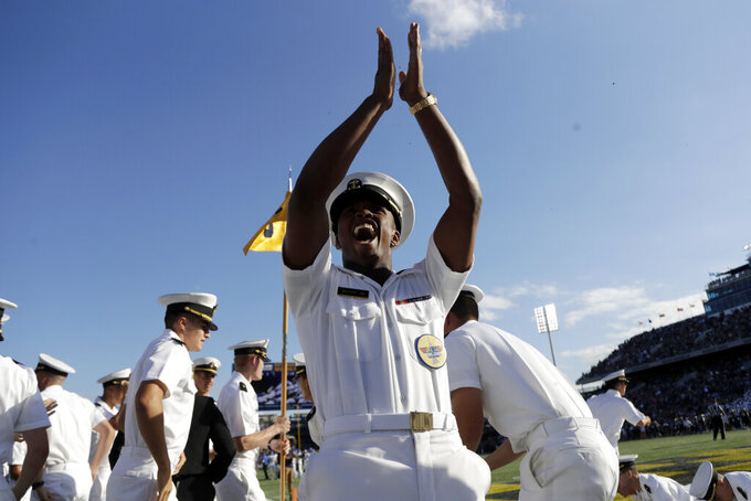 A Navy student reacts after doing pushups following a touchdown by fullback Nelson Smith during the first half of an NCAA college football game against Air Force Saturday, Oct. 5, 2019, in Annapolis, Md. (AP Photo/Julio Cortez)