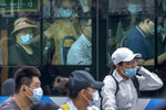 People wearing face masks to protect against COVID-19 ride on a bus during the morning rush hour in Beijing, Wednesday, Aug. 4, 2021. The coronavirus's delta variant is challenging China's costly strategy of imposing near-total isolation on any budding hotspots, prompting warnings from health experts that Chinese leaders who were confident they could keep the virus at bay need a less disruptive approach. (AP Photo/Mark Schiefelbein)
