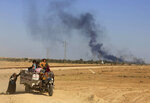 FILE - In this Monday, April 4, 2016 file photo, smoke rises as people flee their homes during clashes between Iraqi security forces and members of the Islamic State group in Hit, Iraq, 85 miles (140 kilometers) west of Baghdad, Iraq.Iraq on Monday, Dec. 10, 2018 celebrated the anniversary of its costly victory over the Islamic State group, which has lost virtually all the territory it once held but still carries out sporadic attacks. (AP Photo/Khalid Mohammed, File)