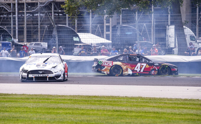 The cars of Aric Almirola (10), left, and Ricky Stenhouse Jr. (47) slide out of control after making contact with a curb at Turn 5 during a NASCAR Cup Series auto race at Indianapolis Motor Speedway, Sunday, Aug. 15, 2021, in Indianapolis. (AP Photo/Doug McSchooler)