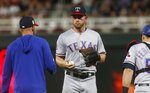 Texas Rangers pitcher Adrian Sampson, center, waits to be removed during the fourth inning of the team's baseball game against the Minnesota Twins on Friday, July 5, 2019, in Minneapolis. (AP Photo/Jim Mone)
