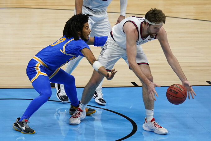 UCLA guard Tyger Campbell, left, tries to steal the ball from Gonzaga forward Drew Timme, right, during the first half of a men's Final Four NCAA college basketball tournament semifinal game, Saturday, April 3, 2021, at Lucas Oil Stadium in Indianapolis. (AP Photo/Michael Conroy)