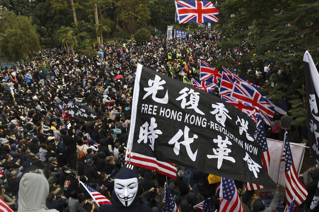 "FILE - In this Sunday, Jan. 19, 2020 file photo, participants wave British and U.S. flags during a rally demanding electoral democracy and call for boycott of the Chinese Communist Party and all businesses seen to support it in Hong Kong. Only five years ago, former British Prime Minister David Cameron was celebrating a ""golden era"" in U.K.-China relations, bonding with President Xi Jinping over a pint of beer at the pub and signing off trade deals worth billions. Those friendly scenes now seem like a distant memory, with hostile rhetoric ratcheting up this week over Beijing's new national security law on Hong Kong. China has threatened ""consequences"" after Britain offered refuge to millions in the former colony. (AP Photo/Ng Han Guan, file)"