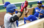 Texas Rangers' Shin-Soo Choo, left, is congratulated by teammates after hitting a solo home run during the first inning of a baseball game against the Los Angeles Angels, Friday, May 24, 2019, in Anaheim, Calif. (AP Photo/Mark J. Terrill)