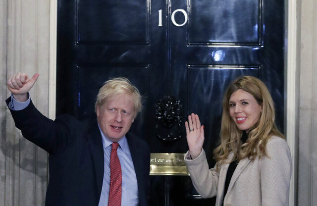 FILE -In this Friday, Dec. 13, 2019 file photo, Britain's Prime Minister Boris Johnson and his partner Carrie Symonds wave from the steps of number 10 Downing Street in London. British Prime Minister Boris Johnson announced Saturday, Feb. 29, 2020 he and his girlfriend Carrie Symonds are expecting a baby in the early summer and are planning to get married. (AP Photo/Matt Dunham, file)