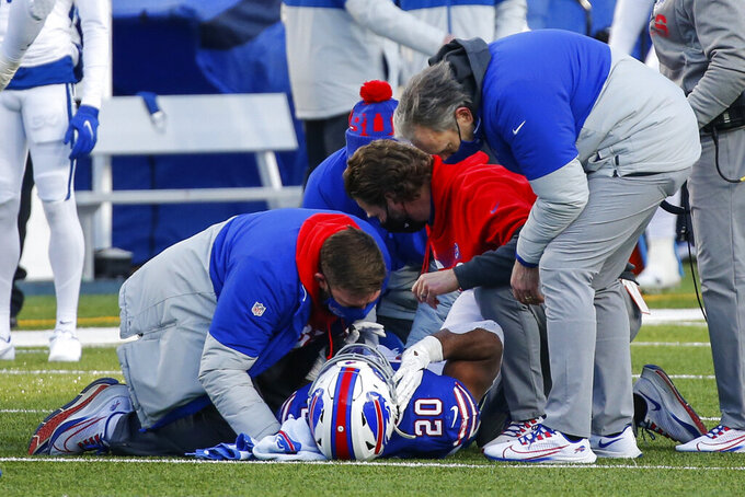 Trainers check on Buffalo Bills' Zack Moss (20) after he was injured on a play during the second half of an NFL wild-card playoff football game against the Indianapolis Colts Saturday, Jan. 9, 2021, in Orchard Park, N.Y. (AP Photo/Jeffrey T. Barnes)