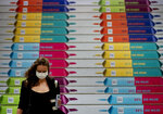 A woman with face mask walks down stairs with chocolate advertising in the main train station after arriving in Frankfurt, Germany, Wednesday, Sept. 16, 2020. (AP Photo/Michael Probst)