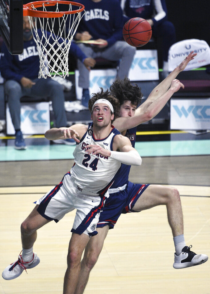 Gonzaga forward Corey Kispert (24) and Saint Mary's forward Kyle Bowen battle for a rebound during the first half of an NCAA semifinal college basketball game at the West Coast Conference tournament Monday, March 8, 2021, in Las Vegas. (AP Photo/David Becker)