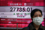A woman walks past an electronic board showing Hong Kong share index outside a local bank in Hong Kong, Wednesday, Feb. 12, 2020. Asian shares were higher Wednesday, although the outbreak of a new virus in the region continued to weigh on investor sentiments. (AP Photo/Kin Cheung)