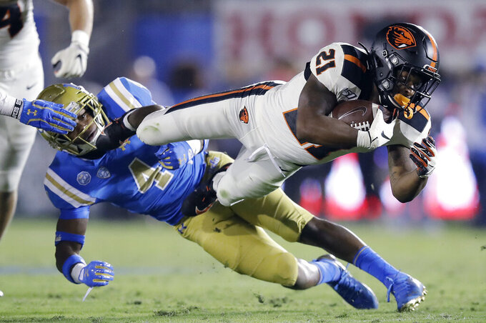 Oregon State running back Artavis Pierce (21) lunges for yardage past UCLA defensive back Stephan Blaylock (4) during the second half of an NCAA college football game Saturday, Oct. 5, 2019, in Pasadena, Calif. (AP Photo/Marcio Jose Sanchez)