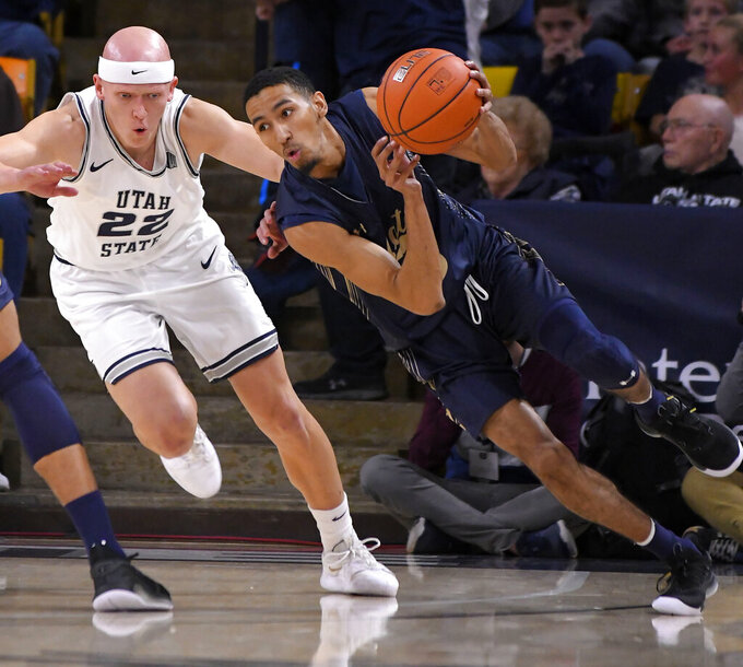 Montana State guard Mychael Paulo dribbles the ball as Utah State guard Brock Miller (22) defends during an NCAA college basketball game Tuesday, Nov. 5, 2019, in Logan, Utah. (Eli Lucero/The Herald Journal via AP)