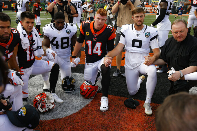 Cincinnati Bengals quarterback Andy Dalton (14) kneels for a post-game prayer after an NFL football game against the Jacksonville Jaguars, Sunday, Oct. 20, 2019, in Cincinnati. (AP Photo/Gary Landers)