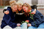 FILE - In this April 21, 1999, file photo, from left, Rachel Ruth, Rhianna Cheek and Mandi Annibel, all 16-year-old sophomores at Heritage High School in Littleton, Colo., console each other during a vigil service to honor the victims of the shooting spree in Columbine High School in the southwest Denver suburb of Littleton, Colo. Twelve students and one teacher were killed in a murderous rampage at the school on April 20, 1999, by two students who killed themselves in the aftermath. (AP Photo/Laura Rauch, File)