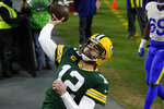 Green Bay Packers quarterback Aaron Rodgers throws the ball to fans after scoring on a one-yard touchdown run against the Los Angeles Rams during the first half of an NFL divisional playoff football game, Saturday, Jan. 16, 2021, in Green Bay, Wis. (AP Photo/Matt Ludtke)