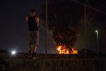 An onlooker watches as a junkyard fire burns in the Kensington neighborhood of Philadelphia, Tuesday, July 10, 2018. (Joe Lamberti/Camden Courier-Post via AP)