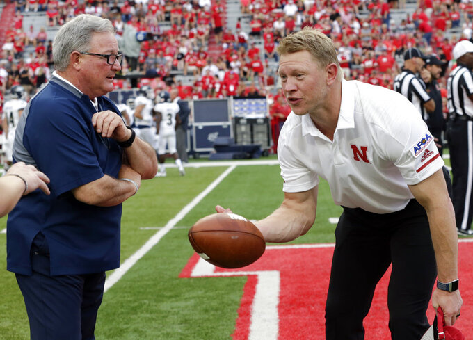 Nebraska head coach Scott Frost, right, tosses the football back to players while talking with Akron head coach Terry Bowden before an NCAA college football game in Lincoln, Neb., Saturday, Sept. 1, 2018. (AP Photo/Nati Harnik)