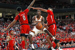 Texas' Andrew Jones (1) lays the ball up between Texas Tech's Kyler Edwards (0) and TJ Holyfield (22) during the first half of an NCAA college basketball game Saturday, Feb. 29, 2020, in Lubbock, Texas. (AP Photo/Brad Tollefson)
