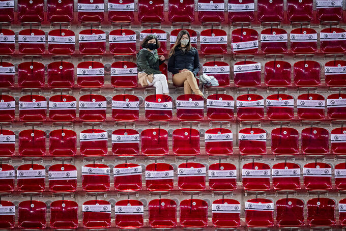 "Spectators follow the match between United States' Shelby Rogers and Ashleigh Barty during the Mutua Madrid Open tennis tournament in Madrid, Spain, Thursday, April 29, 2021. The white banners covering the seats read ""Do not sit here. Keep social distance"". (AP Photo/Bernat Armangue)"