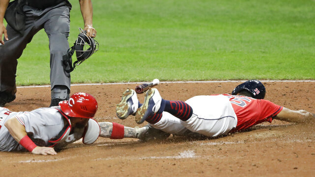 Cleveland Indians' Oscar Mercado, right, slides safely into home plate as Cincinnati Reds' Tucker Barnhart is late on the tag in the fifth inning in a baseball game, Wednesday, Aug. 5, 2020, in Cleveland. (AP Photo/Tony Dejak)