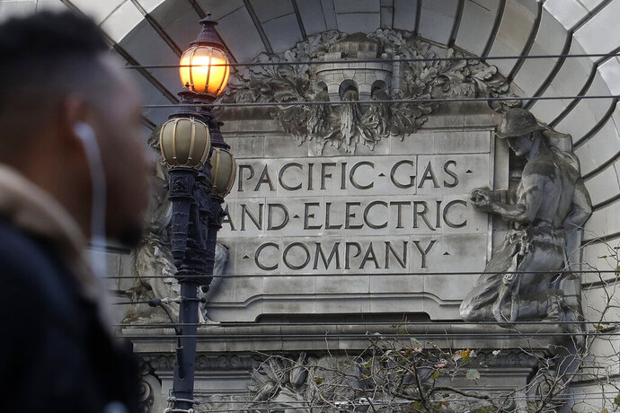 FILE - In this Dec. 16, 2019, file photo, a sign to a Pacific Gas & Electric building is shown in San Francisco. A federal judge is expected opn Friday, June 19, 2020, to approve Pacific Gas & Electric's $58 billion plan for ending its 17-month stint in bankruptcy, clearing the way for the nation's largest utility to begin paying $25.5 billion to cover the losses in a series of horrific wildfires ignited by its long-neglected electrical grid. (AP Photo/Jeff Chiu, File)