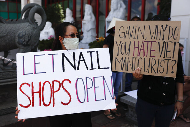 FILE - In this June 8, 2020, file photo nail salon workers hold signs during a protest in Westminster, Calif., to demand California Gov. Gavin Newsom to lift COVID-19 restrictions on nail salons. The services can reopen starting June 19, in counties where health officials allow it. They join a long list of other businesses cleared to reopen in recent weeks, including hair salons, churches and restaurants. (AP Photo/Jae C. Hong, File)