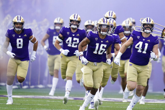 Washington players come out of the tunnel at the start of an NCAA college football game against California, Saturday, Sept. 25, 2021, in Seattle. (AP Photo/Elaine Thompson)