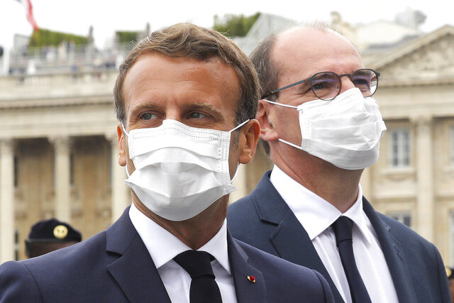 France's President Emmanuel Macron, left, and France's Prime Minister Jean Castex, wear face mask, at the end of the Bastille Day military parade, Tuesday, July 14, 2020 in Paris. Nurses in white coats played the starring role in France's Bastille Day ceremonies Tuesday instead of uniformed soldiers, as the usual grandiose military parade was recalibrated to honor medics who died fighting COVID-19, supermarket cashiers, postal workers and other heroes of the pandemic. (Ludovic Marin, Pool via AP)