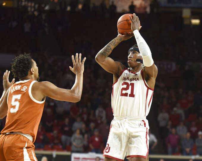 Oklahoma guard Kristian Doolittle (21) shoots the ball over Texas forward Royce Hamm Jr. (5) during the first half of an NCAA college basketball game in Norman, Okla., Tuesday, March 3, 2020. (Kyle Phillips/The Norman Transcript via AP)