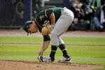 Oakland Athletics starting pitcher Daniel Mengden cleans mud off his shoes as he throws during the first inning of a spring training baseball game against the Seattle Mariners, Friday, Feb. 22, 2019, in Peoria, Ariz. (AP Photo/Charlie Riedel)