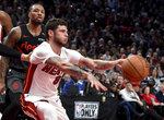 Miami Heat guard Tyler Johnson, right, passes the ball as Portland Trail Blazers guard Damian Lillard defends during the first half of an NBA basketball game in Portland, Ore., Tuesday, Feb. 5, 2019. (AP Photo/Steve Dykes)