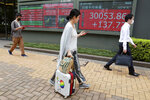 People walk by an electronic stock board of a securities firm in Tokyo, Wednesday, Sept. 8, 2021. Stocks were mixed in Asia on Wednesday after Wall Street closed mostly lower as traders returned from the Labor Day holiday. (AP Photo/Koji Sasahara)