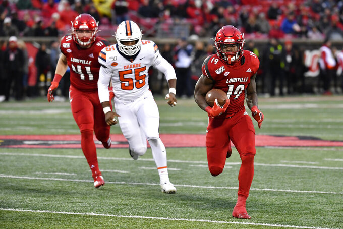 Louisville running back Hassan Hall (19) is pursued by Syracuse defensive lineman Kendall Coleman (55) during the first half of an NCAA college football game in Louisville, Ky., Saturday, Nov. 23, 2019. (AP Photo/Timothy D. Easley)