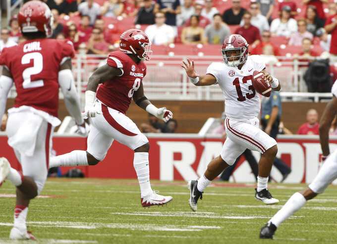 Alabama quarterback Tua Tagovailoa (13) tries to get away from Arkansas defender De'Jon Harris in the first half of an NCAA college football game Saturday, Oct. 6, 2018, in Fayetteville, Ark. (AP Photo/Michael Woods)