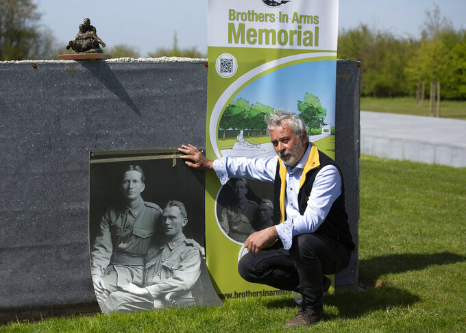 """Johan Vandewalle sits near a photo of Australian brothers and World War I soldiers John """"Jack"""" and Jim Hunter at the Brothers in Arms Memorial in Zonnebeke, Belgium, Thursday, April 22, 2021. Johan Vandewalle is leading a team of volunteers that has almost finished a 40 meter long memorial to Australian John """"Jack"""" Hunter in Flanders Fields in Belgium, where Anzac forces also fought, some 2,750 kilometers (1,700 miles) west from Gallipoli along the immense frontline. On another Anzac Day turned lonesome by the global pandemic, solitary actions show all the more how the sacrifices of Australia and New Zealand during World War I are far from forgotten. (AP Photo/Virginia Mayo)"""