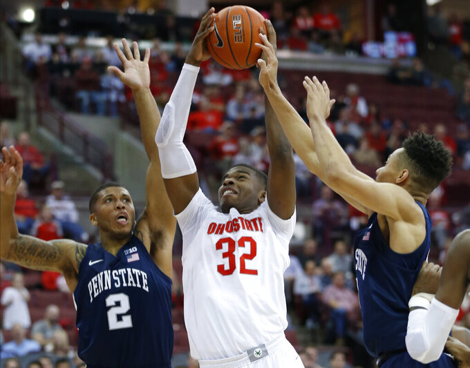 Ohio State's E.J. Liddell, center, grabs a rebound in between Penn State's Myles Dread, left, and Seth Lundy during the second half of an NCAA college basketball game Saturday, Dec. 7, 2019, in Columbus, Ohio. Ohio State beat Penn State 104-74. (AP Photo/Jay LaPrete)