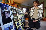 """FILE -  In this Dec. 9, 2011, file photo, Jane Clementi, right, the mother of Tyler Clementi, looks at family photographs of her son as her husband Joseph Clementi, back left, the father of Tyler Clementi, speaks to a reporter in their home in Ridgewood, N.J.  Declaring """"God is on your side,"""" a Roman Catholic cardinal, an archbishop and six other U.S. bishops issued a statement Monday, Jan. 25, 2021, expressing support for LGBT youth and denouncing the bullying often directed at them. It was released by the Tyler Clementi Foundation, named for the Rutgers University student who took his own life in 2010 after being targeted by online harassment. (AP Photo/Mel Evans, File)"""
