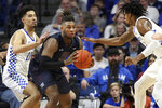Fairleigh Dickinson's Elyjah Williams, center, looks for an opening between Kentucky's Johnny Juzang, left, and Keion Brooks Jr. during the second half of an NCAA college basketball game in Lexington, Ky., Saturday, Dec. 7, 2019. (AP Photo/James Crisp)