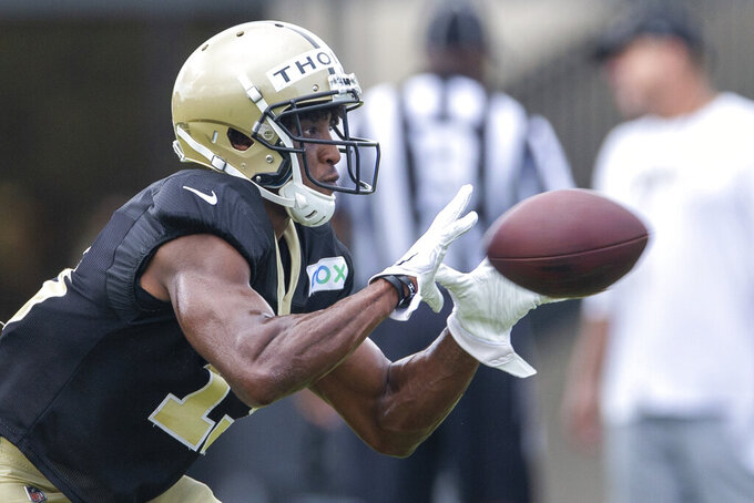 New Orleans Saints wide receiver Michael Thomas (13) catches a New Orleans Saints quarterback Drew Brees (9) pass during an NFL football training camp practice at the Ochsner Sports Performance Center in Metairie, La., Friday, Aug. 28, 2020. (David Grunfeld/The Advocate via AP, Pool)