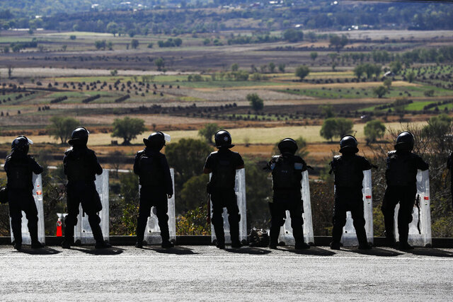 In this Feb. 6, 2020 photo, state police stand guard along the road leading into Uruapan, Michoacan state, Mexico. Uruapan, a city of about 340,000 people, is in Mexico's avocado belt, where violence has reached shocking proportions. In Uruapan, cartels are battling for territory and reports of killings are common, such as the gun massacre last week of three young boys, a teenager and five others at an arcade in what had been a relatively quiet neighborhood. (AP Photo/Marco Ugarte)