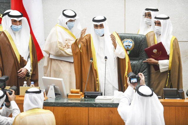 The new Emir of Kuwait Sheikh Nawaf Al Ahmad Al Sabah, center, performs the constitutional oath at the Kuwaiti National Assembly in Kuwait, Wednesday, Sept. 30, 2020. Kuwait's Sheikh Nawaf was sworn in Wednesday as the ruling emir of the tiny oil-rich country, propelled to power by the death of his half-brother after a long career in the security services. (AP Photo/Jaber Abdulkhaleg)