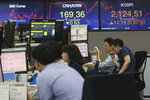 Currency traders watch monitors at the foreign exchange dealing room of the KEB Hana Bank headquarters in Seoul, South Korea, Friday, June 26, 2020. Asian stock markets followed Wall Street higher on Friday after U.S. regulators removed some limits on banks' ability to make investments. (AP Photo/Ahn Young-joon)